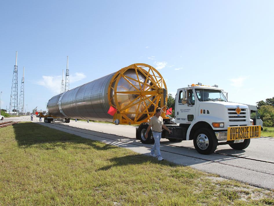 Atlas V first stage is transported by truck to the launch pad.