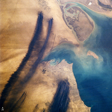 streaks of carbon-black smoke smear south/southwest from multiple oil fires in Kuwait.