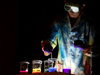 surrounded by darkness, a man in tie-dyed lab coat and goggles pours colored liquids into beakers