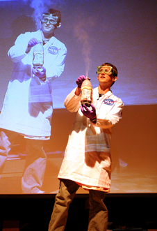 a man in a tie-dyed lab coat and goggles vents vapors from a 2-liter bottle as his doppleganger does the same on the projection screen behind him.