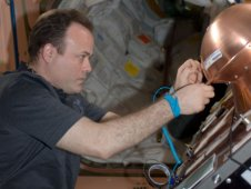 International Space Station astronaut Ron Garan works with the Reentry Breakup Recorder.