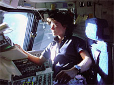 Sally Ride looks out the space shuttle window from the flight deck