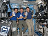 Three crew members hold space station drink bags