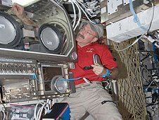 Expedition 30 Commander Dan Burbank works with hardware inside the Microgravity Science Glovebox aboard the International Space Station. (NASA)