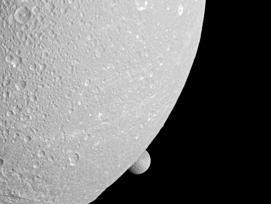 Saturn's moon Mimas peeps out from behind the larger moon Dione