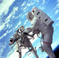 Astronaut Steven L. Smith stands on the mobile foot restraint at the end of the remote manipulator system (RMS).