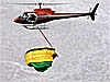 Helicopter flies with a hook above a parachute and catches the chute