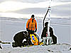 Three men work with a drill on the ice-covered ground