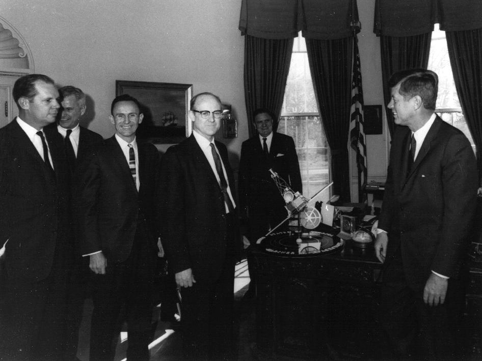 This 1961 photo shows Dr. William H. Pickering, (center) JPL Director, presenting a Mariner spacecraft model to President John F. Kennedy, (right).