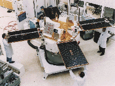 ACE satellite under construction. Scientists are holding the solar arrays.