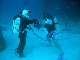 A NEEMO aquanaut dives using a U.S. Navy EX-14 suit.