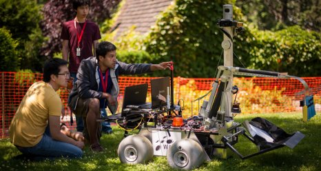 Teammates from the University of Waterloo, Canada, team work with their robot on the practice field at the Sample Return Robot Challenge.