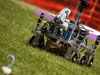 A six-wheeled robot sits in a grassy field