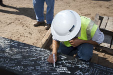 A workers signs the beam