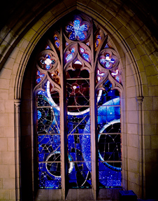 The 'Space Window' was designed by St. Louis artist Rodney Winfield and fabricated under his supervision. Whirling stars and orbiting planets are depicted in orange, red and white on a deep blue and green field