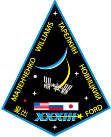 A four-sided mission patch shaped like an inverted kite. The crew's names are around the edges. Flags of the U.S., Russia and Japan are near the bottom, below the space station