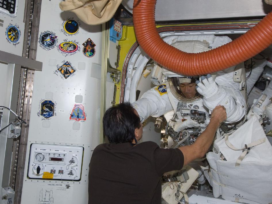 Astronaut Joe Acaba assists spacewalker Akihiko Hoshide