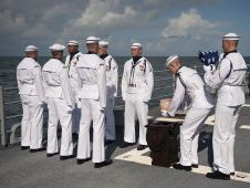U.S. Navy personnel carry the cremated remains of Apollo 11 astronaut Neil Armstrong during a burial-at-sea service aboard the USS Philippine Sea (CG 58), Friday, Sept. 14, 2012, in the Atlantic Ocean. Armstrong, the first man to walk on the moon during the 1969 Apollo 11 mission, died Aug. 25.