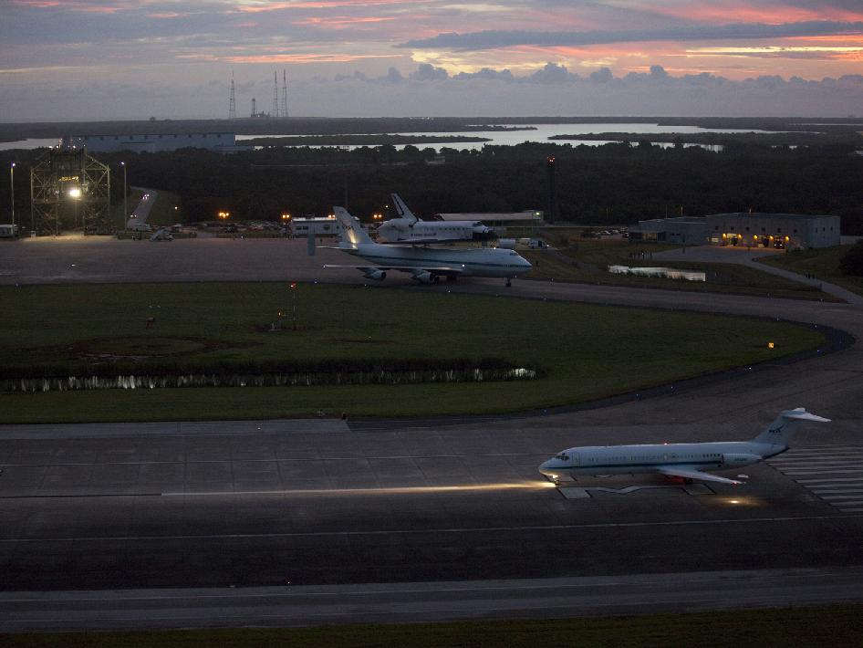 A pathfinder aircraft leads NASA's Shuttle Carrier Aircraft with space shuttle Endeavour toward the runway