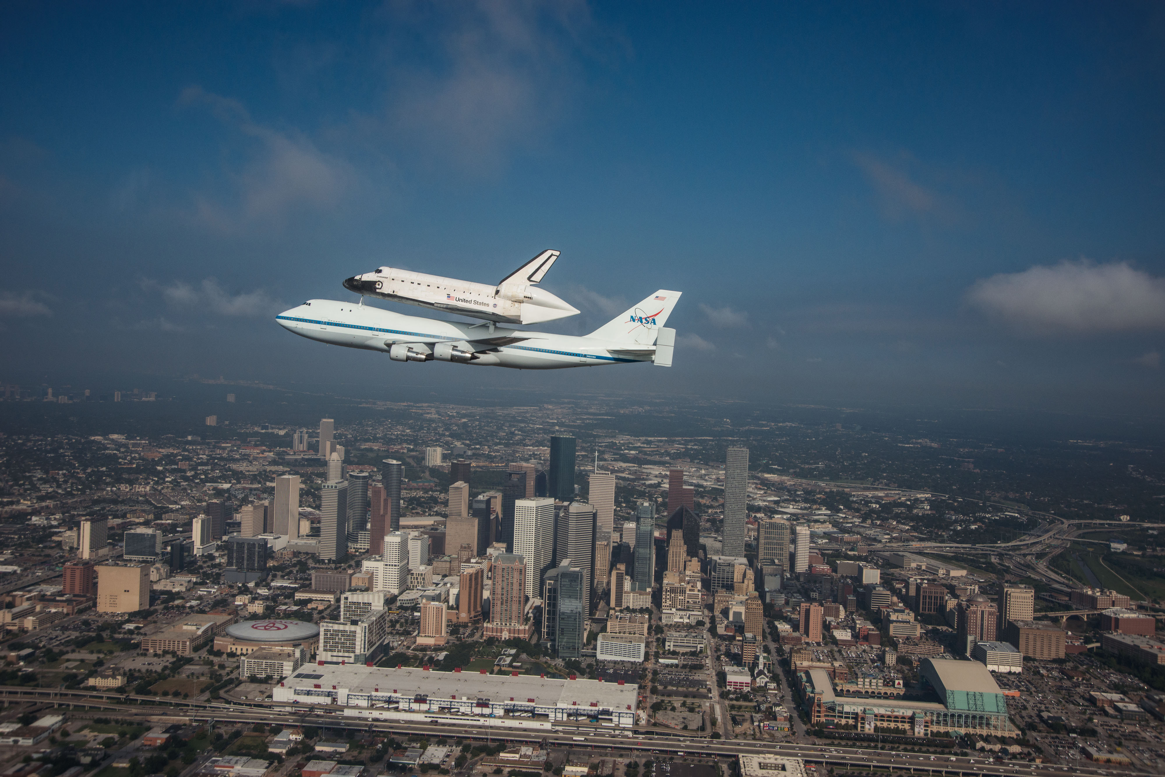 Image of the a NASA space craft attached to a jet flying over the city of Houston, Texas.