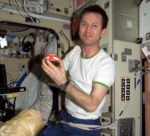 Expedition 5 Flight Engineer Sergei Treschev holds a can of Russian food