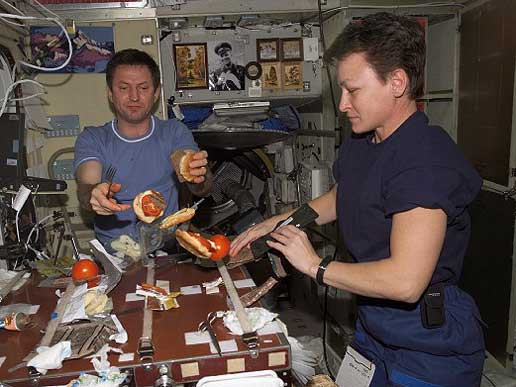 Expedition 5 crewmembers Sergei Treschev and Peggy Whitson share a meal