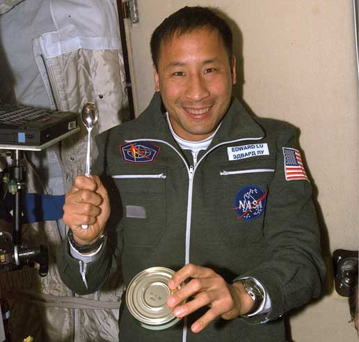 Expedition 7 NASA ISS Science Officer Ed Lu prepares to eat