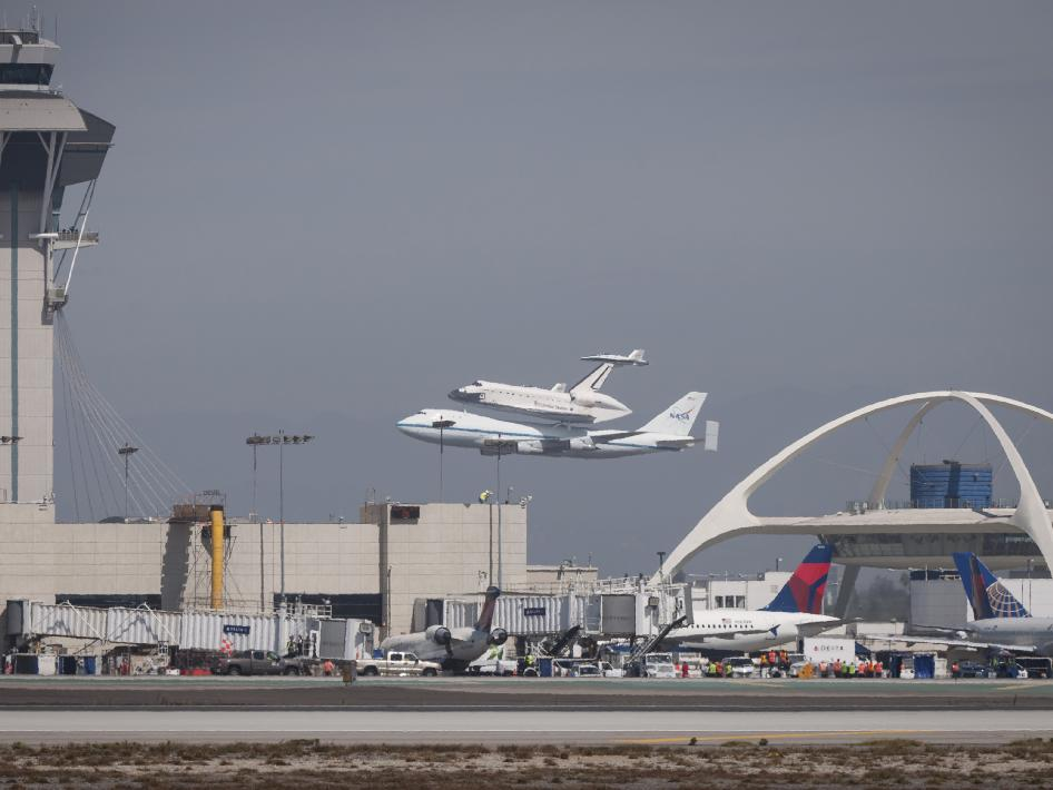 Space shuttle Endeavour, mounted atop a NASA 747 Shuttle Carrier Aircraft (SCA) performs a low flyby past the tower at Los Angeles International Airport, Friday, Sept. 21, 2012.