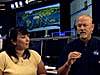 A woman and a man sit in NASA's Mission Control Center