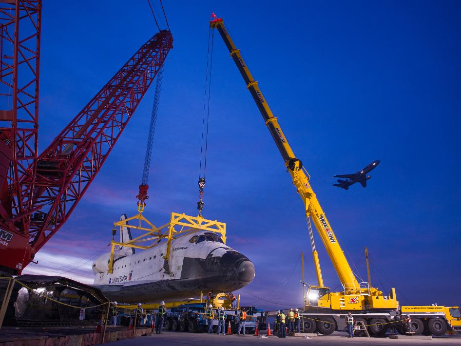 An airplane is seen taking off as space shuttle Endeavour is secured to the Over Land Transporter (OLT) in the early morning hours of Saturday, Sept. 22, 2012, at Los Angeles International Airport.