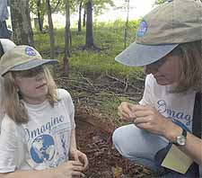 A blind, 12-year-old girl named Amelia (left) and her instructor Robin House kneeling down and touching the soil on the ground