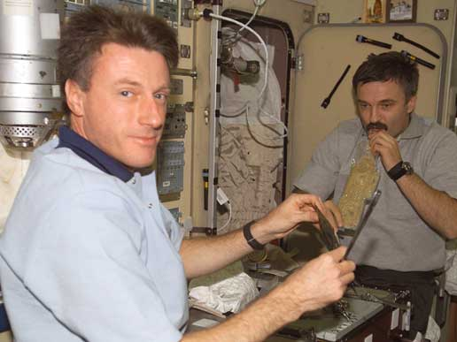 Expedition 8 crewmembers Mike Foale and Alexander Kaleri enjoying a meal.