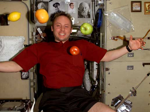 Expedition 9 crewmember Mike Fincke juggles fruit with the help of micro-gravity.