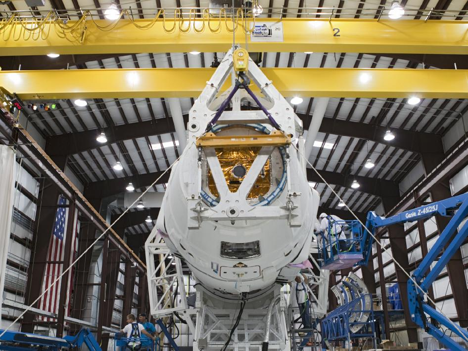 Technicians attach the Dragon capsule to a Falcon 9 rocket at the SpaceX facility at Cape Canaveral Air Force Station, Fla., during preparations for the CRS-1 mission.
