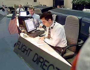 Flight Director Paul Hill, foreground, and CAPCOM Stephen Frick monitor communications during a simulation