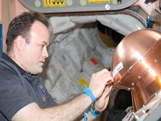 Expedition 28 Flight Engineer Ron Garan applying copper tape to exposed activation ports on the ReEntry Breakup Recorder. (NASA)