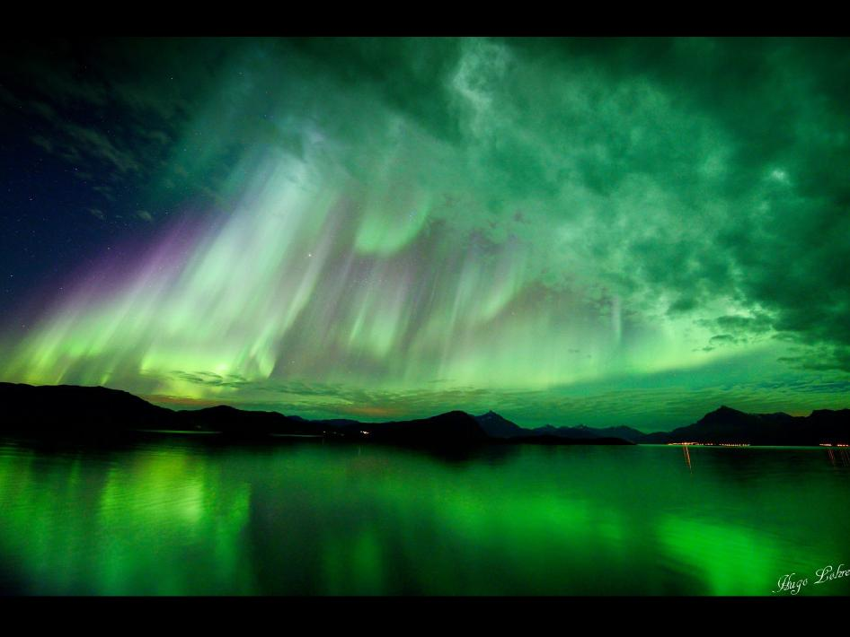 Aurora that appears to be casting rays of green sunlight through the clouds over Lekangsund, Norway, on Oct. 10, 2012.