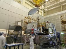 Engineers check on the GPM spacecraft after successful completion of its first comprehensive performance test. The silver disc and drum (center) is the GPM Microwave Imager, and the large block on the base is the Dual-frequency Precipitation Radar. The tall golden antenna is the High Gain Antenna fo
