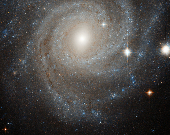 an off-center spiral galaxy, fringed by several nearby bright stars