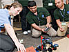 Three students work on a small robotic rover