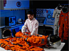 Engineer works with orange-colored astronaut suits