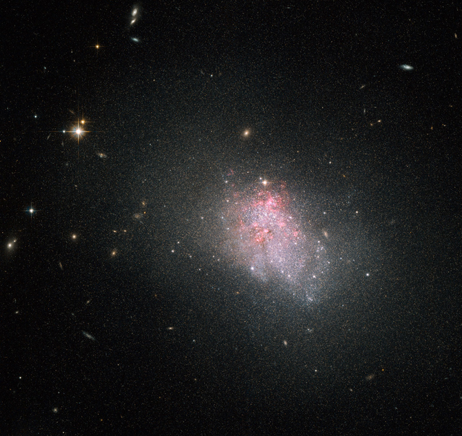 a thick asymmetrical mass of stars surrounding a splotch of pink, star-forming areas, with more orderly galaxies shining through the haze