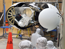 An Orbital Sciences technician completes final checks of NASA's NuSTAR inside the Orbital processing facility before the Pegasus payload fairing is secured around it.