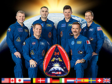 The Expedition 34 crew poses in front of a picture of a sunrise taken from space