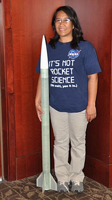 A woman holds a tall model rocket and wears a t-shirt with words It's Not Rocket Science (oh wait, yes it is)