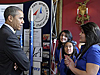 President Obama talks with three girls while standing in front of a rocketry display