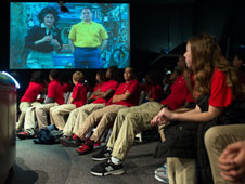 Students in red shirts look up at a large screen showing astronauts Sunita Williams and Kevin Ford speaking from the space station
