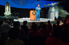 Wearing a blue flight suit, Leland Melvin stands in front of a lectern displaying the Smithsonian Institute seal and speaks to audience