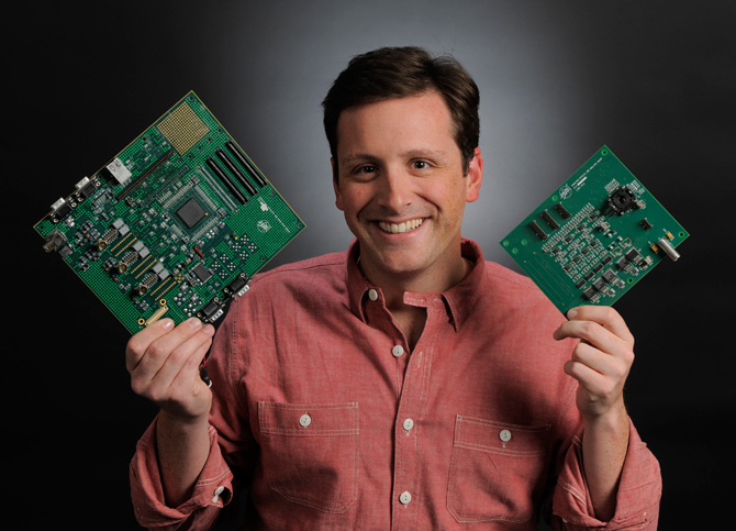 Jonathan Pellish holds a Goddard-developed digital test board (larger, left) and the IRAD-developed daughter card containing the analog-based data-processing integrated circuit.