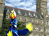 Rubber chicken in astronaut flight suit stands in front of a college building